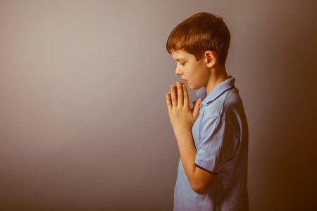 prayer background: boy teenager European appearance in a blue shirt brown hair hung his head closed his eyes on a gray background, prayer retro