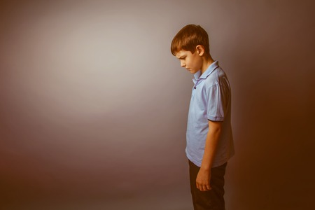 sadness: boy teenager European appearance in a blue shirt brown hair hung his head on a gray background, sadness retro