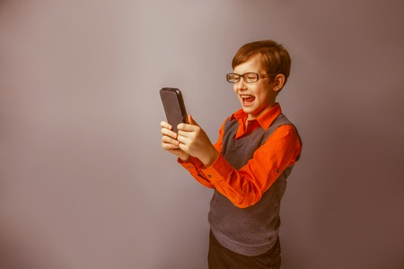 plays: European-looking boy  of ten  years in  glasses  holding tablet in hand, plays  on a blue background retro