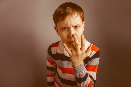 licking finger: European-looking boy  of ten years licks his finger on a gray background retro