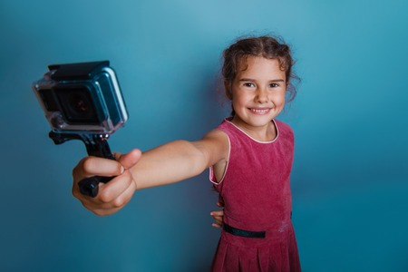 Girl child holding a camera in his hand shooter shouts gray  background