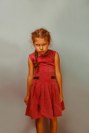 frowns: Girl European appearance  decade angry frowns on blue background retro