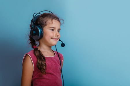 decade: Girl European appearance decade listening to music  with headphones on a blue background Stock Photo