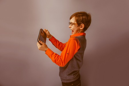 plays: European-looking boy  of ten  years in glasses holding tablet in hand, plays on a blue background retro Stock Photo