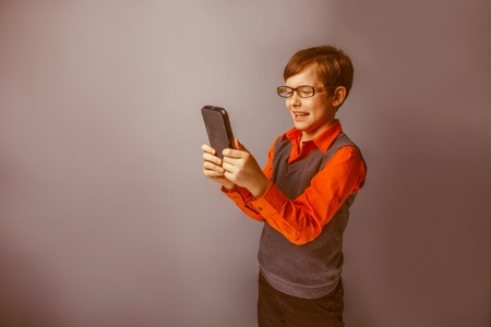 plays: European-looking  boy of ten years in glasses holding tablet in hand, plays, pleasure on a blue background retro Stock Photo