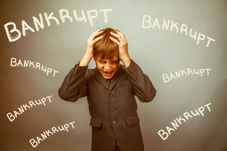 fails: Teen boy businessman fails bankrupt holding his head inscription studio background retro