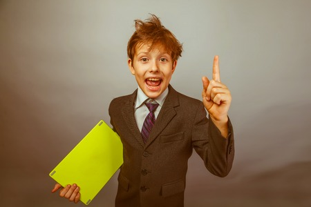 wild hair: Teen boy businessman in a suit raised his finger up wild hair holding a tablet retro