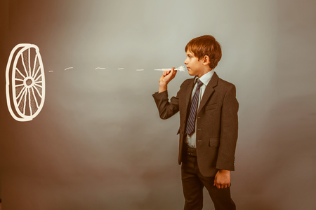 DARTS: Teen boy businessman throwing darts at a target dart on a blue background studio retro