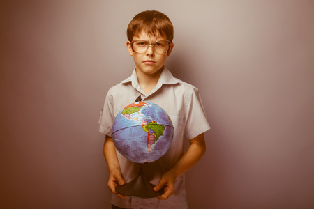 frowned: teenager boy brown hair European appearance in sunglasses holding a globe and frowned on a gray background, thoughtful retro