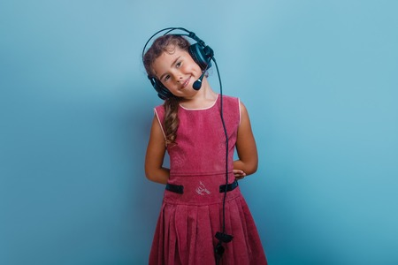 decade: Girl European  appearance decade listening  to music with headphones on a blue background