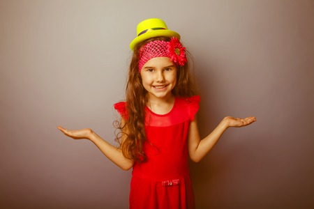 seven years: Girl European appearance haired child of seven years in a bright yellow dress hat smiling on gray background, spread her hands retro Stock Photo