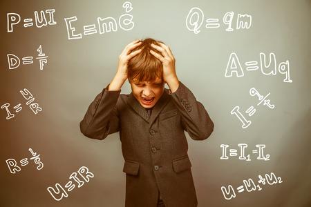 fails: Teen boy scientist fails holding his head formula physics science studio background experiencing problems retro