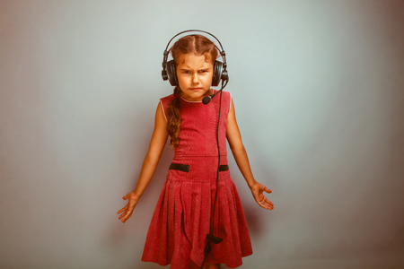 dissatisfied: Teen girl child dissatisfied evil in headphones with a microphone sideways in profile on a blue background photo studio retro