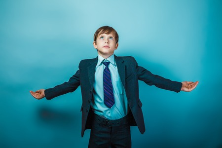European appearance teenager boy in a business suit opened his arms in hand businessman on gray background, freedom