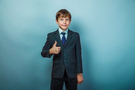 boys: European appearance teenager boy in a business suit shows a sign yes on a gray background, the seriousness of the