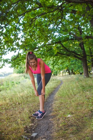 respite: Girl European appearance young brown-haired woman in a pink shirt and gray tights with white headphones leaned corrects pants in the woods, nature, sport, respite Stock Photo