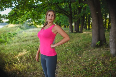 put forward: Girl European appearance young brown-haired woman in a pink shirt and gray tights with white headphones put his hand on the waist, looking forward to the outdoors, sports, recreation