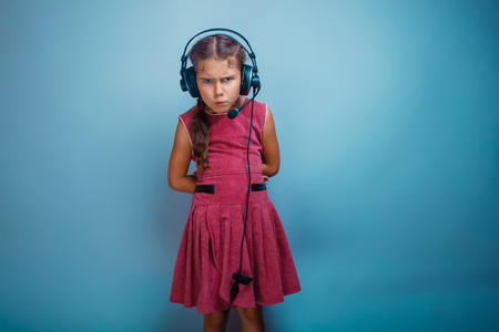 frowned: he girl child is seven years old in a pink dress with black headphones on a gray background frowned, anger, resentment