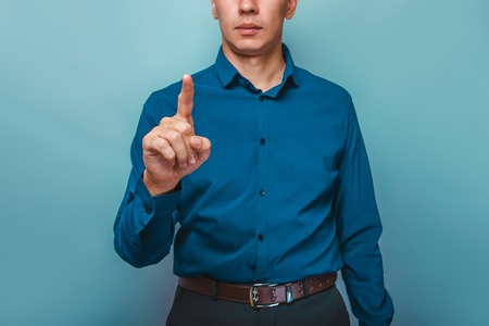 press button: a man can be seen  half-face shows a finger on a gray background Stock Photo