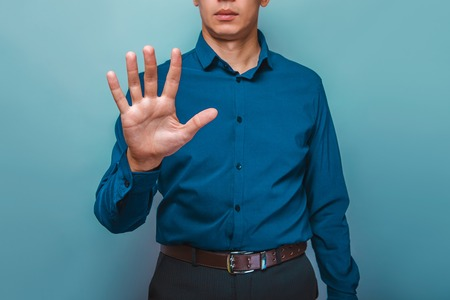 fingers: a man can be seen half-face shows the 5 fingers hand on a gray background