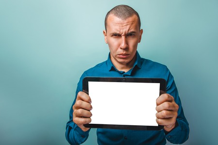 frowns: a man of European appearance thirty years shows a tablet frowns on a gray background