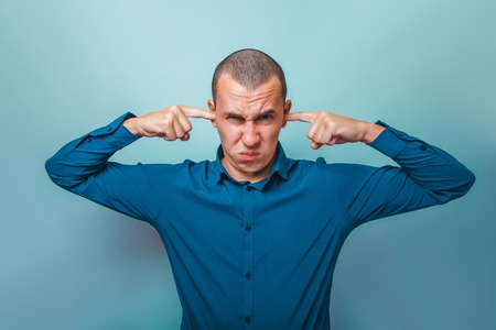frowns: a man of European appearance thirty years, his hands covering his ears frowns on a gray background Stock Photo