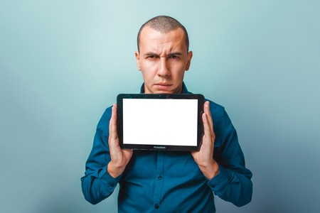 frowns: a man of European appearance thirty years, holding a tablet frowns on a gray background