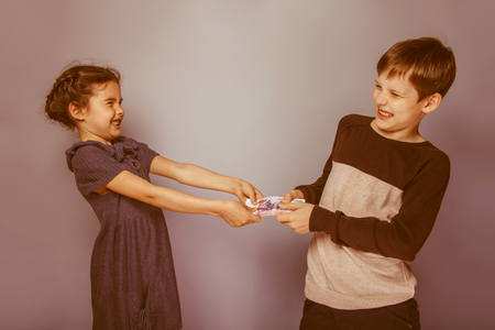 bleed: teenage boy and girl holding money bills in his hands bleed each other on gray  background retro Stock Photo