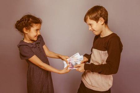 bleed: teenage boy and girl holding money bills in his hands bleed each other on gray background retro