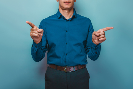 baffled: a  man can not see the person shows index fingers in opposite directions on a gray background Stock Photo