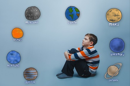 frowned: boy sitting frowned and hugged her knees looking at the planets of the solar system astronomy Stock Photo
