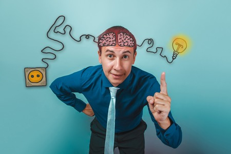 booster: businessman smiling and raised his index finger up brain booster charge plug wires and sketch infographics Stock Photo