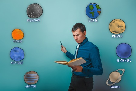frowned: male businessman shows his hand to the side and with enthusiasm reads the book frowned planet of the solar system astronomy Stock Photo