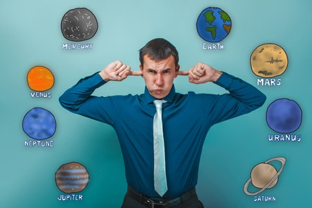unwillingness: man winced and plugged ears forefingers unwillingness to listen to the planets of the solar system astronomy Stock Photo