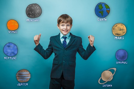 grins: Teen boy businessman grins and shows its strength hands joyful planet of the solar system astronomy
