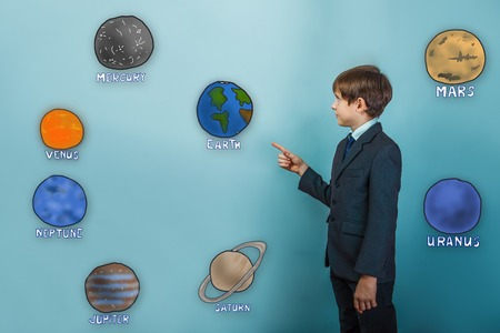 specifies: Teen boy businessman in a suit specifies hand on the planets of the solar system astronomy Stock Photo