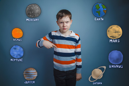 frowned: Teen boy frowned dissatisfied points a finger down the planets of the solar system astronomy Stock Photo