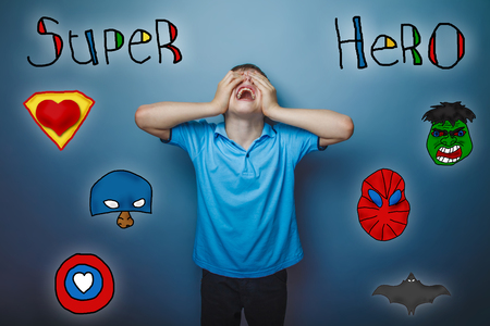 screaming head: boy screaming his head back and closed his eyes fingers superhero super power at the photo studio Icons hero Stock Photo
