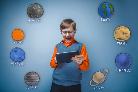 grins: Teen boy with glasses grins and runs on a gray plate planets of the solar system astronomy