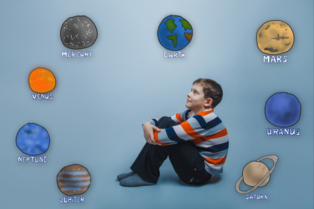 hugging knees: Teen boy sitting hugging her knees and looking at the planets of the solar system astronomy Stock Photo