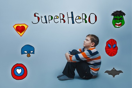 hugging knees: boy sitting on the floor hugging his knees and looking up frowned superhero super power at the photo studio Icons hero Stock Photo