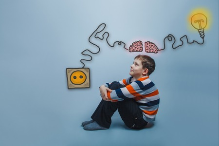 booster: Teenage boy sitting on the floor hugging his arms legs and looks up and smiles thinking brain booster charge charging plug wire and sketch infographics