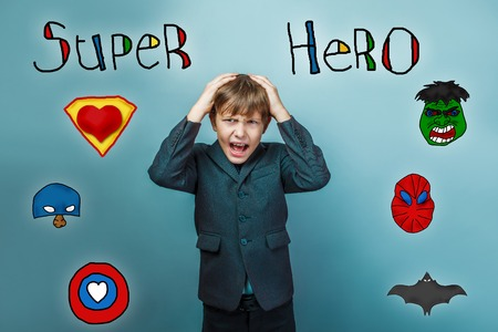 opened mouth: Businessman screaming teenage boy opened his mouth keeps his hands behind his head superhero super power at the photo studio Icons hero Stock Photo