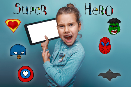 mouth open: girl holding a tablet and shouting his mouth open super hero super power at the photo studio Icons hero Stock Photo