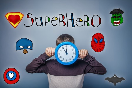 face covered: Teen boy covered his face with clock keeps their hands superhero super power at the photo studio Icons hero