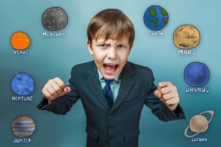 business style: Teenage boy in a business style suit screaming and clenching his fists planets of the solar system astronomy Stock Photo
