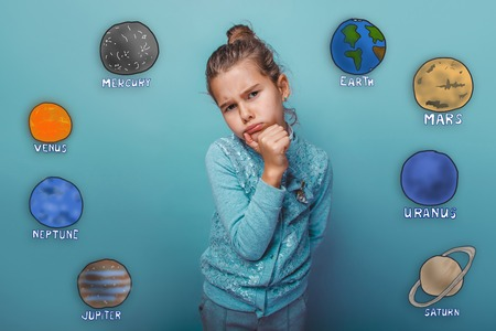 frowned: Teenage girl is offended frowned lips stuck out planets in our solar system astronomy Stock Photo