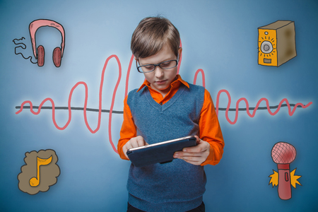 enthusiastically: Teenage boy in glasses enthusiastically working on the tablet sound wave music radio sketch symbol Stock Photo
