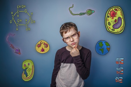 parasite: boy with glasses holding his chin ponders icons biology education formation of the embryo cell parasite Stock Photo
