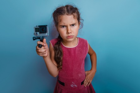 frowns: teen girl of European appearance seven years, holding the camera displeased frowns on a blue background